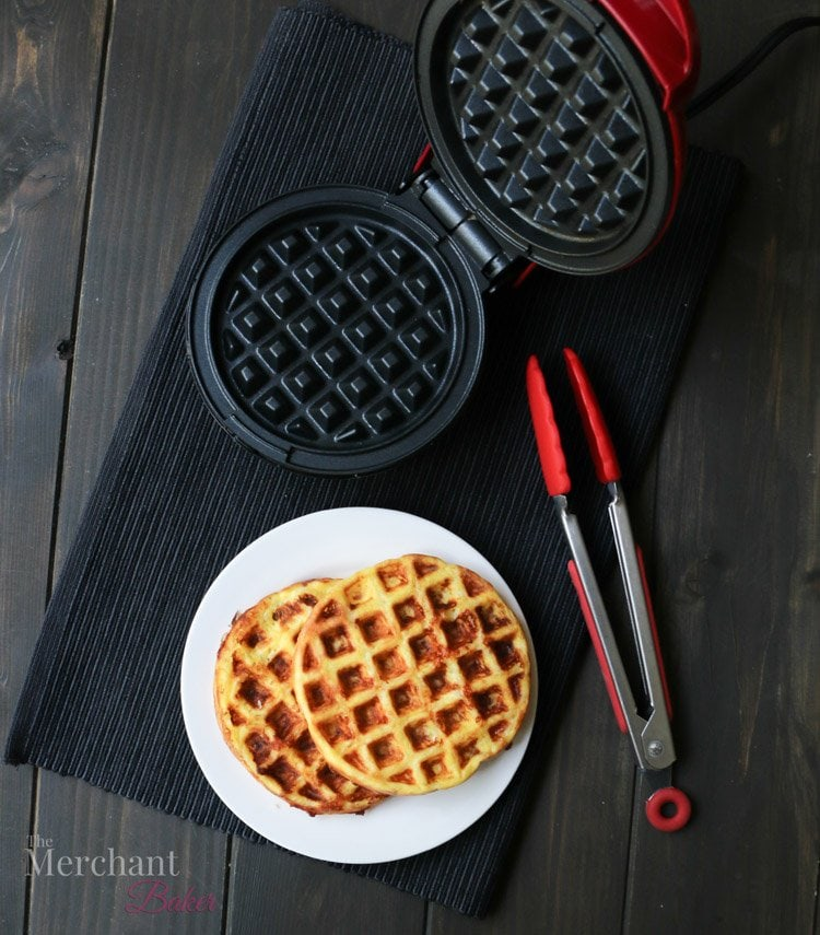 Overhead photo of Chaffles on a plate next to a dash mini waffle maker by themerchantbaker.com