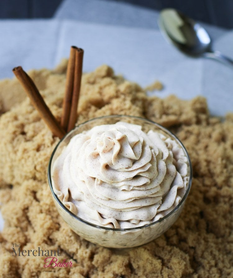 An overhead view of Brown Sugar Cinnamon Whipped Cream Cream Cheese Frosting in a bowl on a mound of brown sugar with cinnamon sticks by themerchantbaker.com