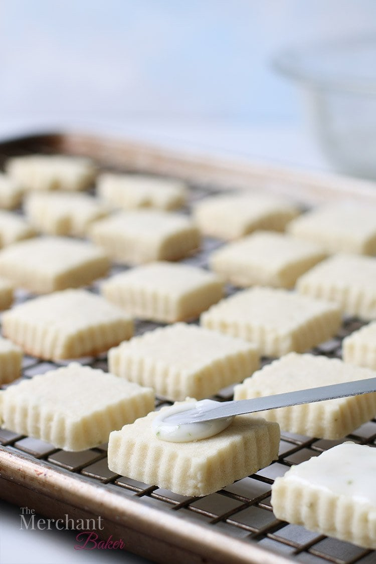 A close up view of icing being spread on a square meltaway cookie