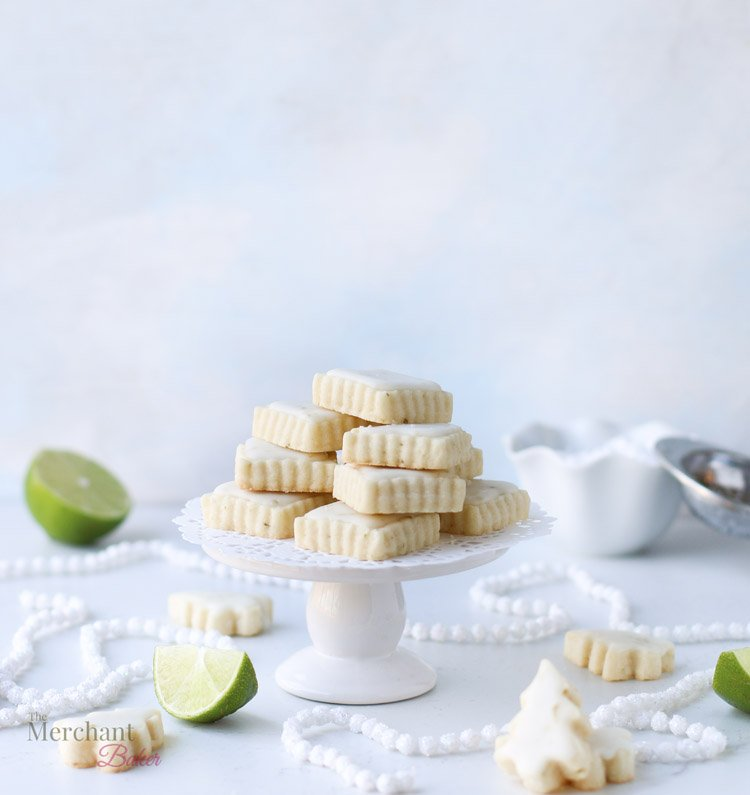A stack of lime meltaway cookies on a small cake stand surrounded by tree shaped cookies and pieces of cut up lime