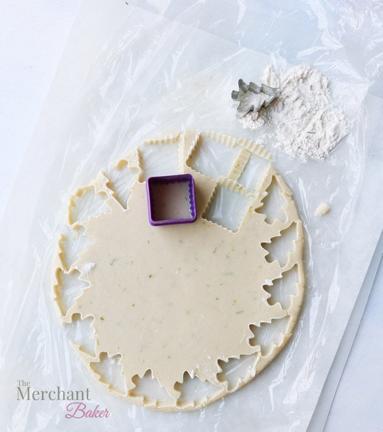 An overhead view of cutting shapes out of rolled out cookie dough