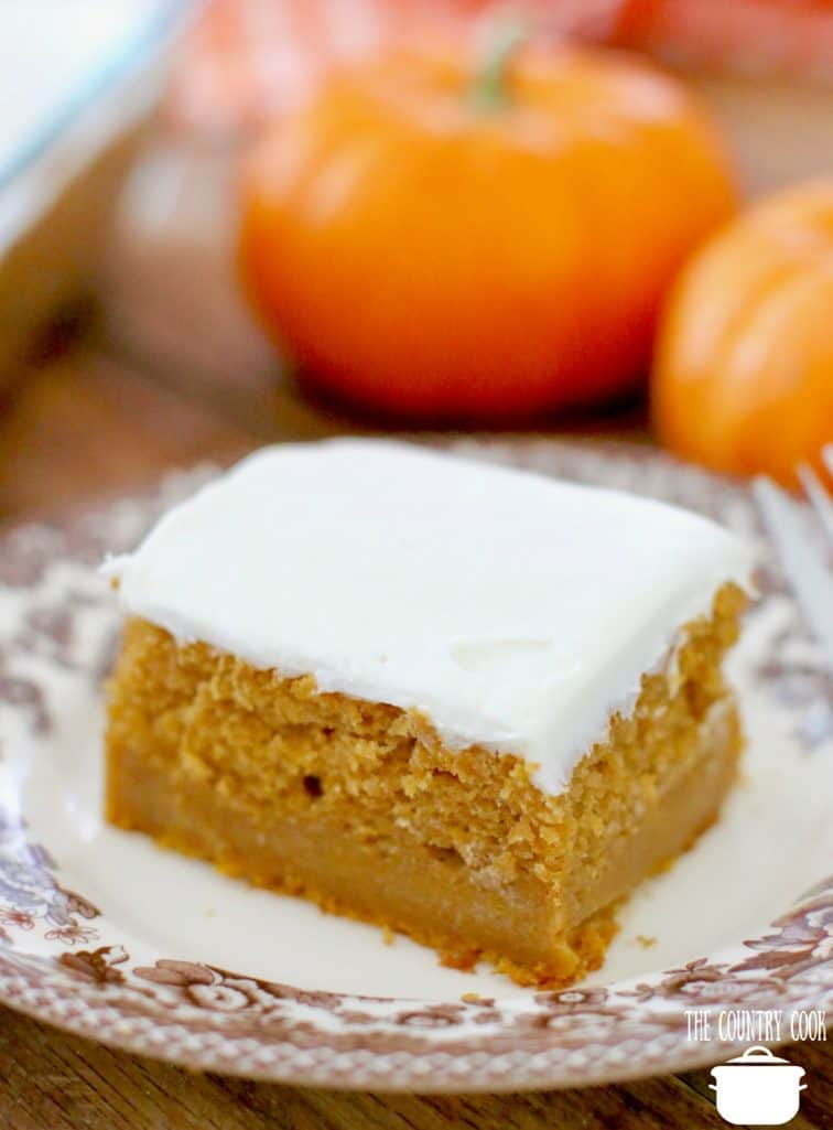 slice of Easy Pumpkin Pie Cake on a dessert plate with mini pumpkins in the background