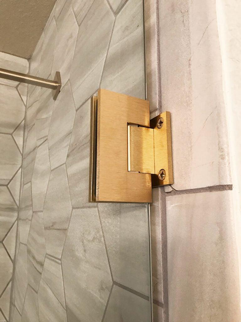 Brass shower hardware complements grey tile in remodel of bathroom in Golden