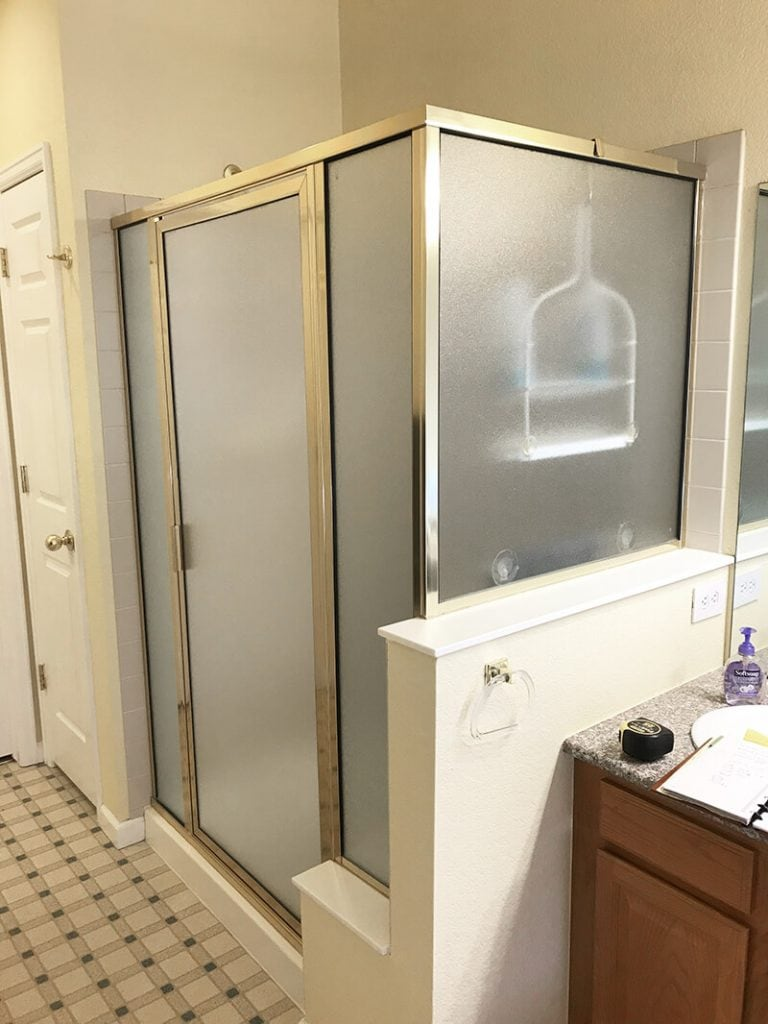 Shower with frosted glass and gold before remodel of bathroom in Lakewood