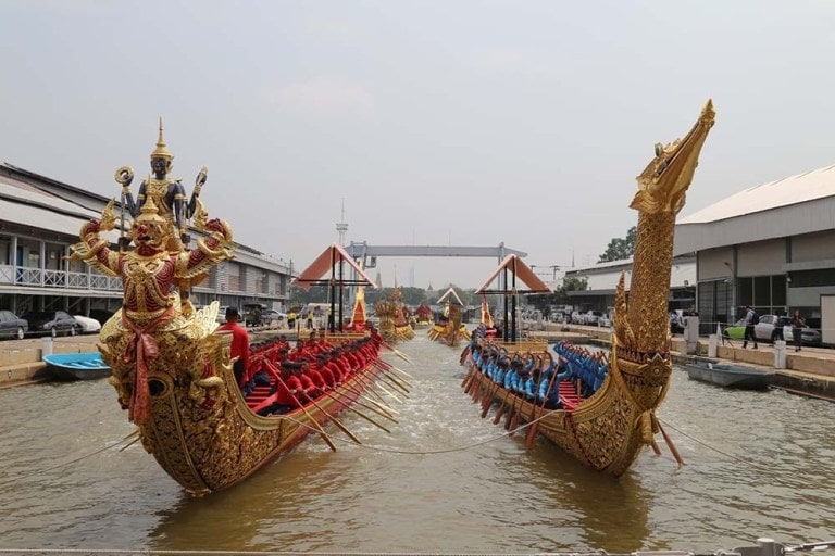 Two gilded long boats sit in river facing camera. One has swan-shaped, tall bow. The other has two creatures, one on top of the other.