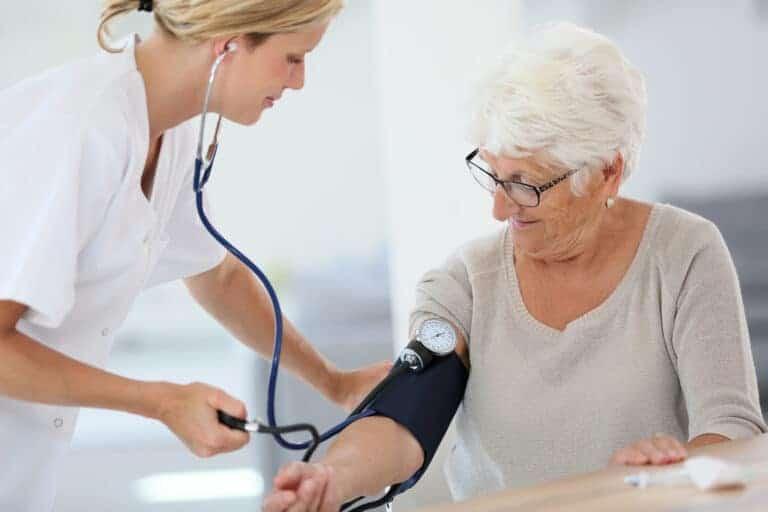Pflegerin misst Blutdruck bei älterer Dame