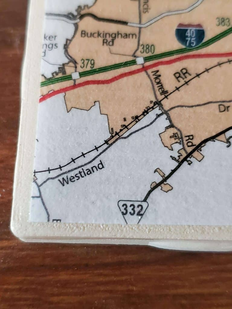 Corner of a DIY map coaster, showing border of tile and map cut out.