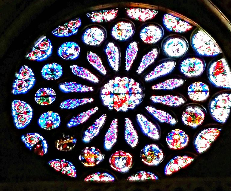 Rose window filled with multi-colored stained glass is silhouetted by interior walls.