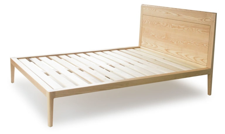 overall view of ash platform bed no. 1. Ash wood is blonde in color and has a open grain texture, similar to oak. The bed has smooth continuous edges, thin legs, and a sculpted, angled headboard.