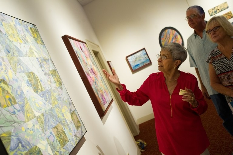Docent points out details in painting to visiting patrons.