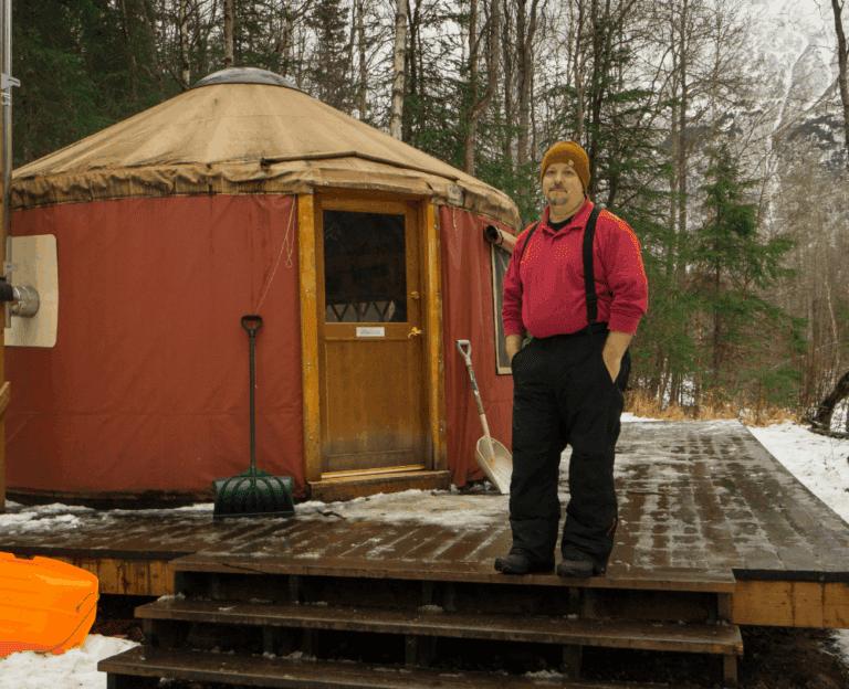 mark standing in front of yurt