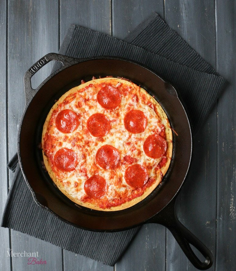 An overhead image of baked pepperoni Socca Pizza in an iron skillet by themerchantbaker.com