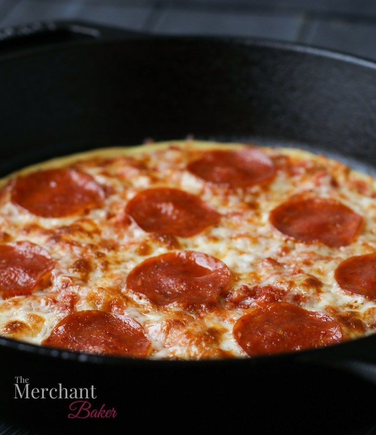 Side angle view of pepperoni Socca Pizza in an iron skillet by themerchantbaker.com