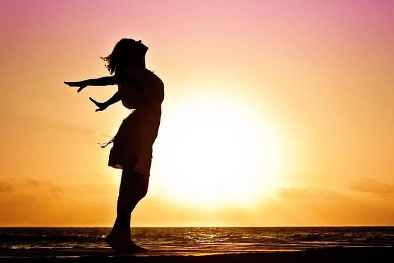 silhouette of woman standing on beach with arms out at sunset