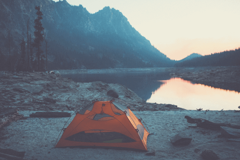 tent on lakeshore in mountain valley