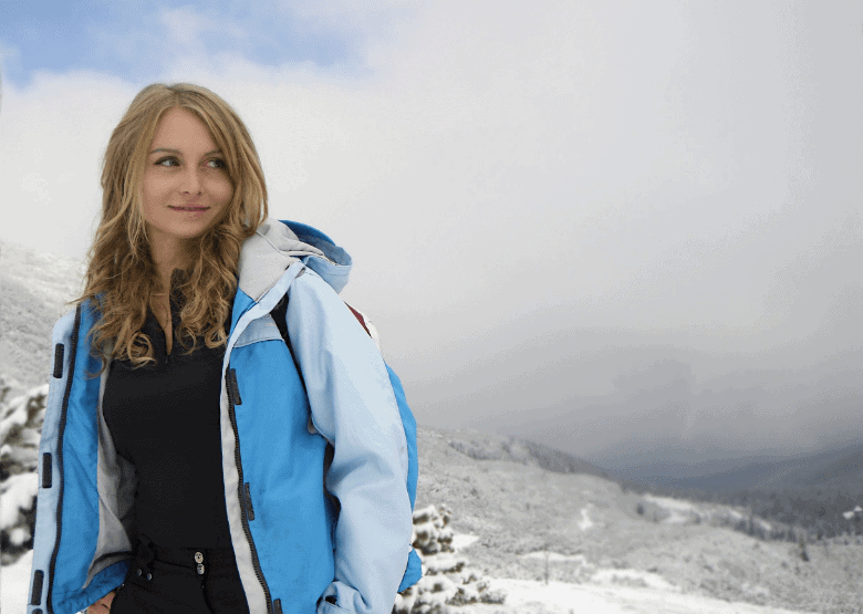 young woman in cold weather on top of a mountain