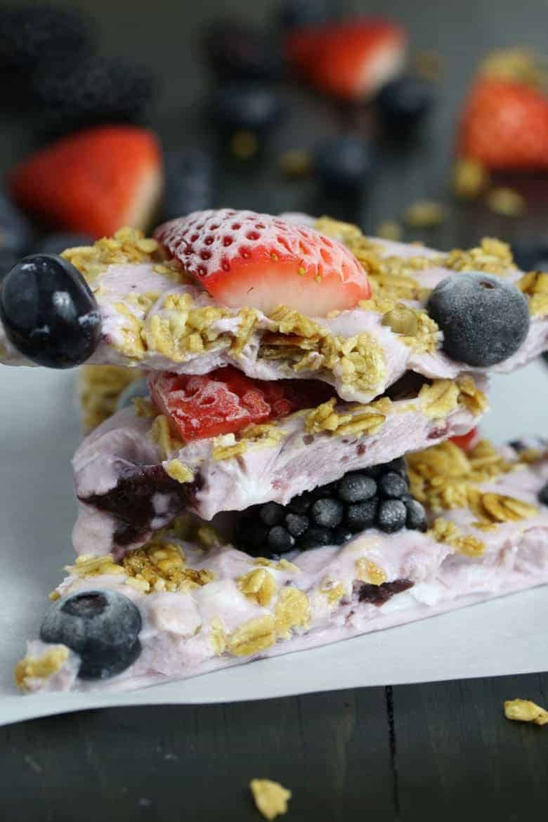 This triple berry granola frozen yogurt breakfast bark is perfect for busy mornings. It's like eating a make-ahead breakfast parfait popsicle and is great for feeding a crowd! Bark up close