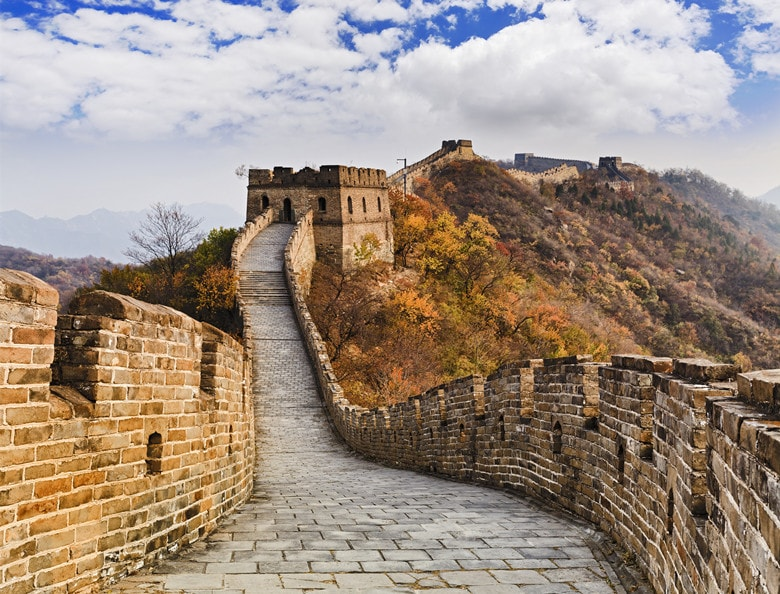 The Great wall of China ancient national architectural landmakrs high in Mutianyu mountains under blue sky tracing away