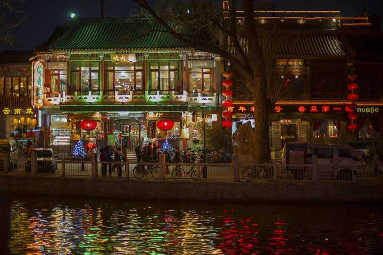 Houhai in Beijing at night. The lake with reflections of lamps and neon lights is in the foreground. In the backround are crowds of people in front of multiple bars and restaurant with multiple logos.