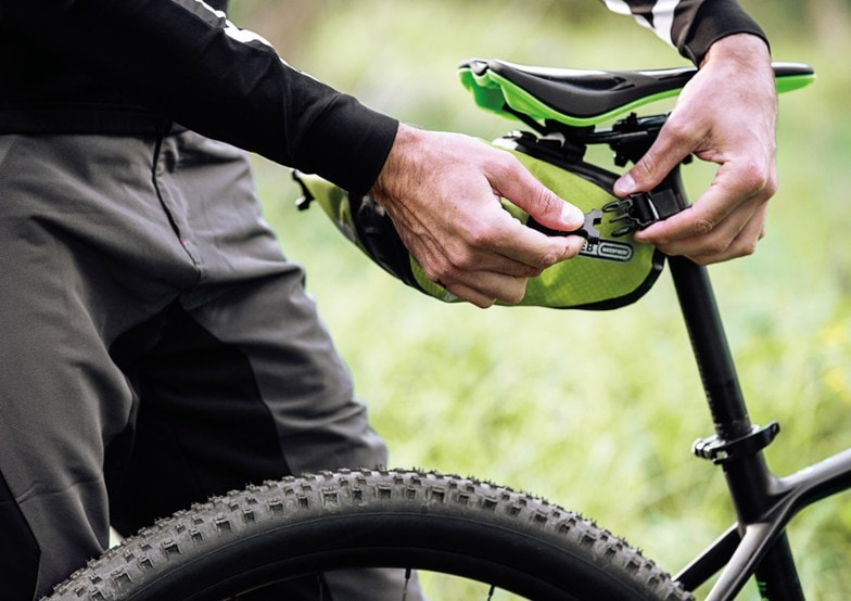 Man's hands attaching an Ortlieb saddle bag to a bike