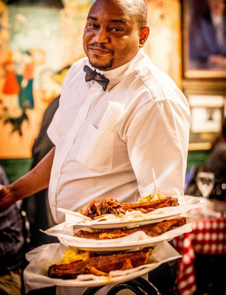 waiter in white shirt and bow tie holds 3 plate of memphis-style BBQ in one arm looking directly at camera