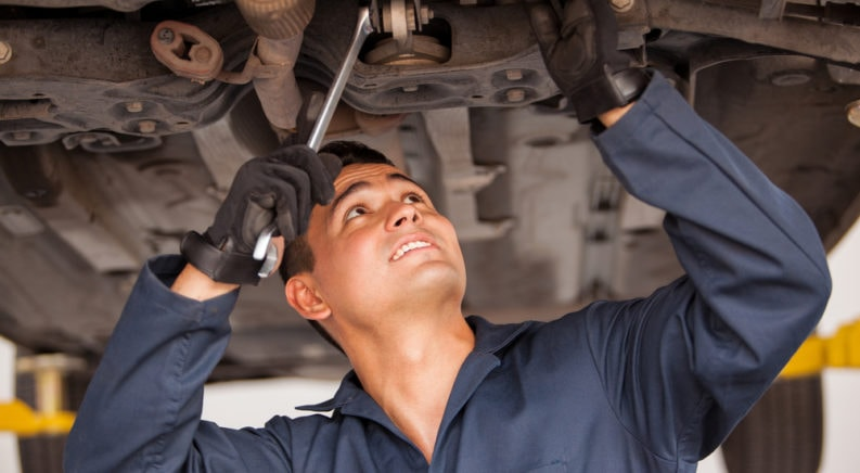Mechanic under a vehicle performing a car inspection