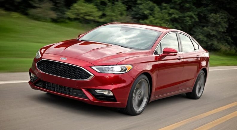 Looking for Used Cars? Here's a red 2017 Ford Fusion driving on a road