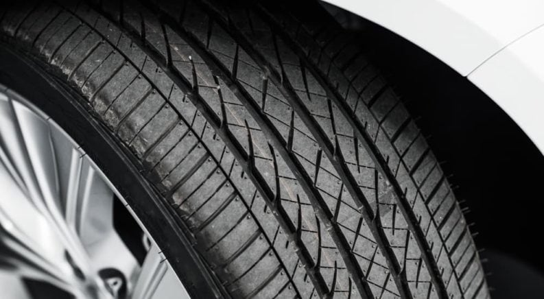 A close up of one of the tires on a white car is shown.