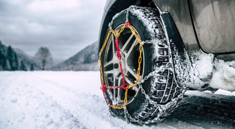 A closeup of tire chains is shown on a car tire in the snow.