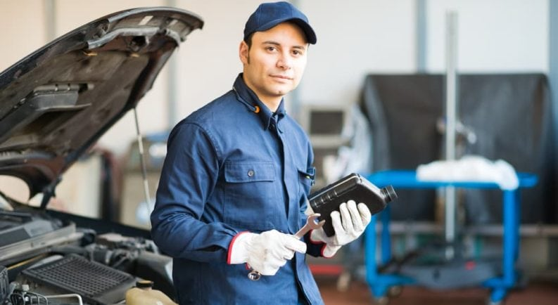 A mechanic is shown holding a bottle of oil.