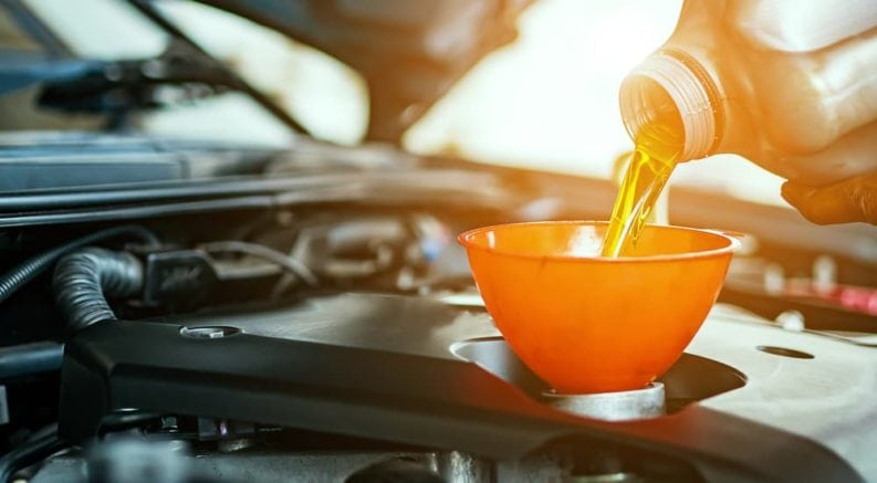New oil is shown being poured into a car after a customer searched, 'Quick Oil Change Near Me'.
