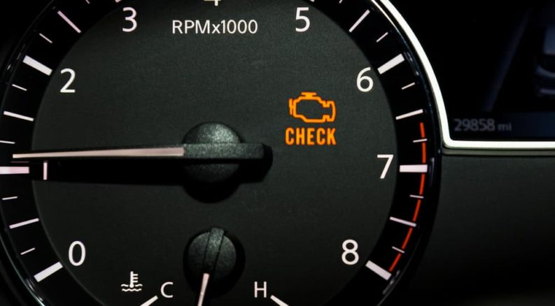 A close up of an orange check engine light is shown.