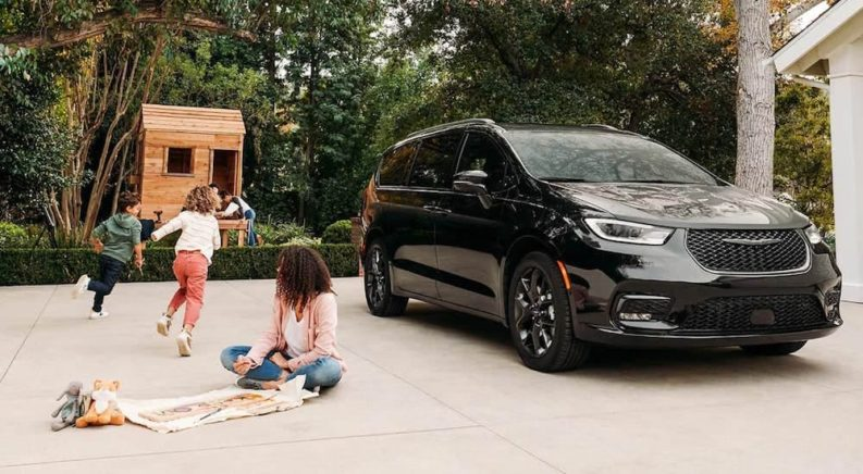 A black 2021 Chrysler Pacifica is parked in a driveway with children playing near it.