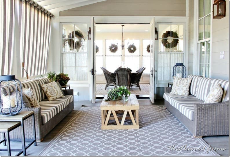 French doors open to this dining room porch with woven lounge sofas and soft striped linen curtains