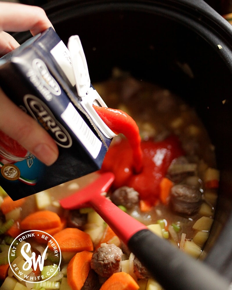Passata being poured into the slow cooker