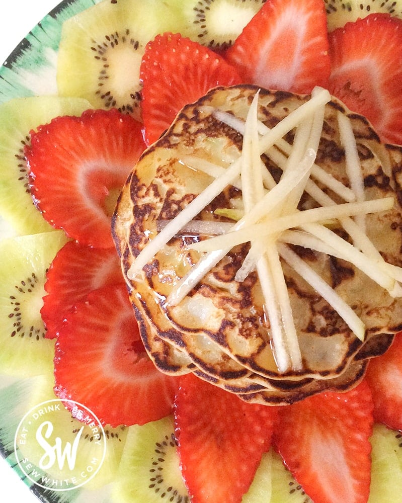 golden brown fluffy apple pancakes topped with grated apple and maple syrup