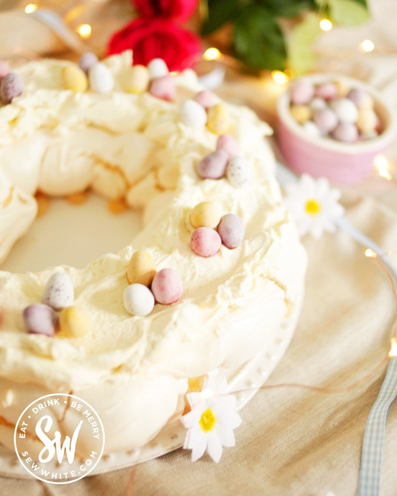 Ready to serve the Easter meringue decorated with fake flowers and mini eggs