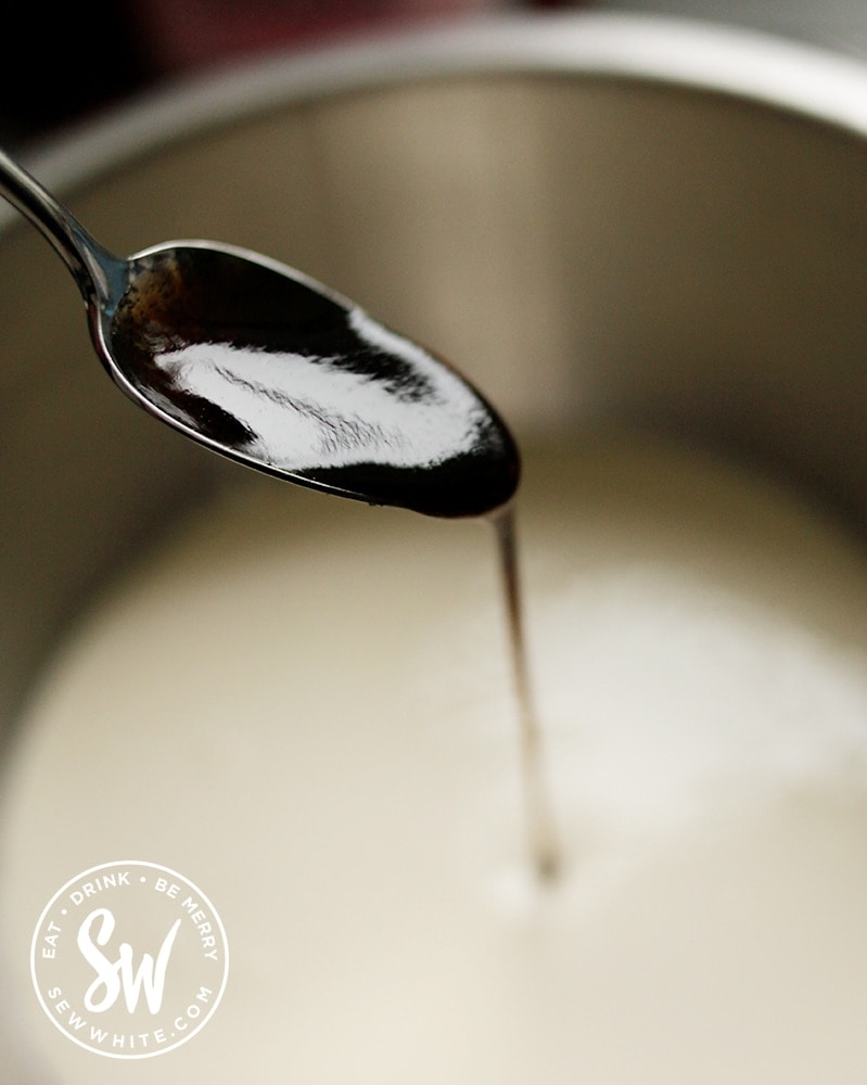 Vanilla paste being spooned into a cream mix