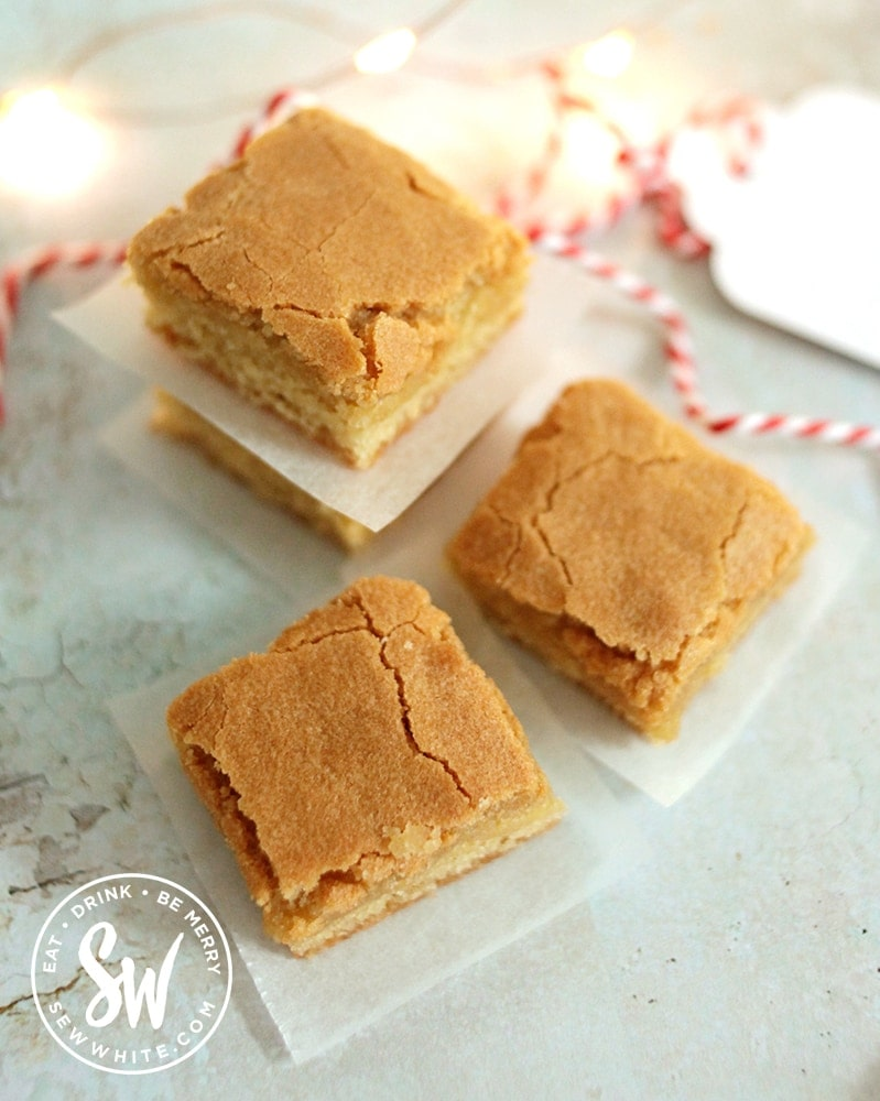 Easy Blondie Recipe to make at home. Freshly sliced blondie on a blue surface