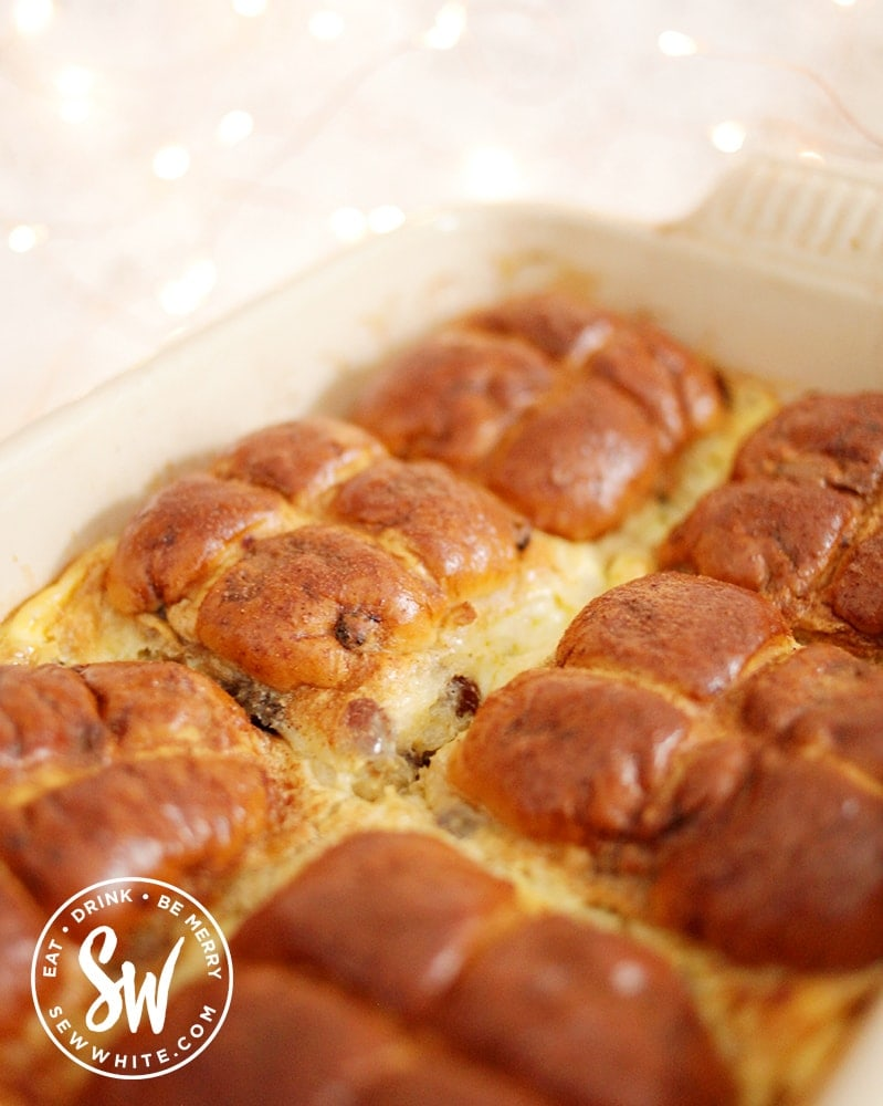 The finished golden brown Hot Cross Bun Dessert with custard and a sprinkle of cinnamon.