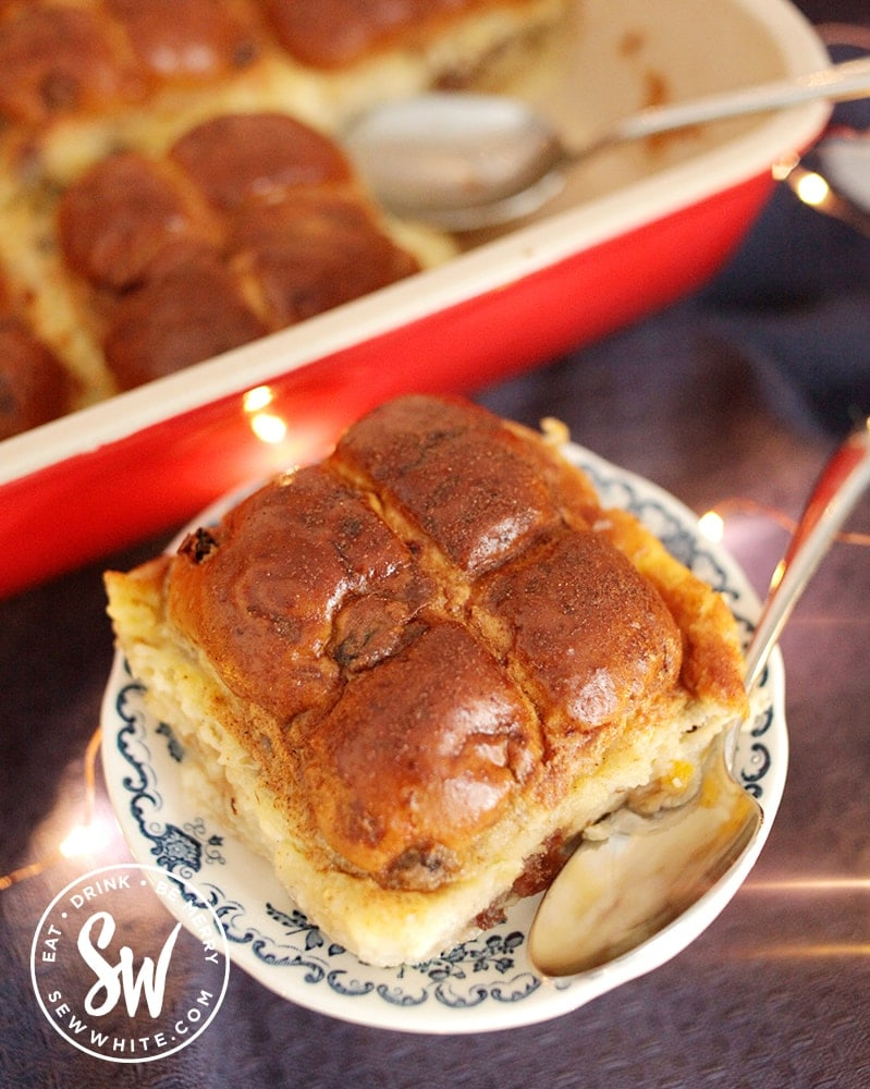 Oven baked Hot Cross Bun Dessert cooked in a red Le Creuset oven proof dish. Hot cross bun bread and butter pudding slice on a little plate
