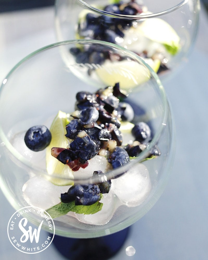 squashed fresh blueberries with lime and mint in a large glass for the Blueberry Gin and Tonic Recipe
