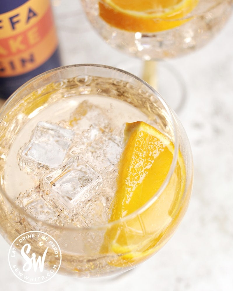 top view of a Jaffa Cake Gin Spritz with ice cubes and slice of orange