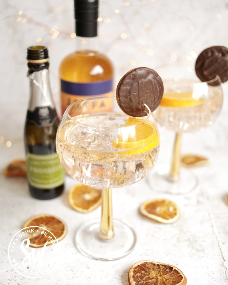 golden orange Jaffa Cake Gin Spritz in a gin glass decorated with jaffa cakes and surrounded by dried oranges.