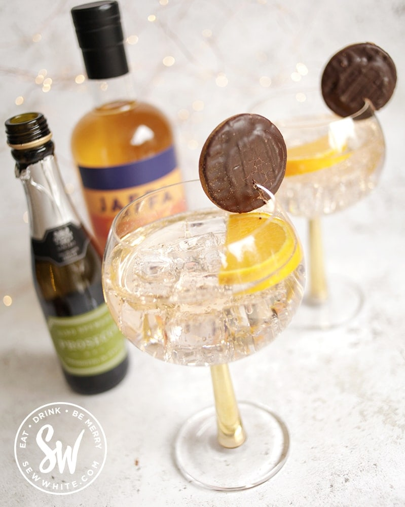 Jaffa Cake Gin Spritz in gold stemmed glasses, decorated with jaffa cakes