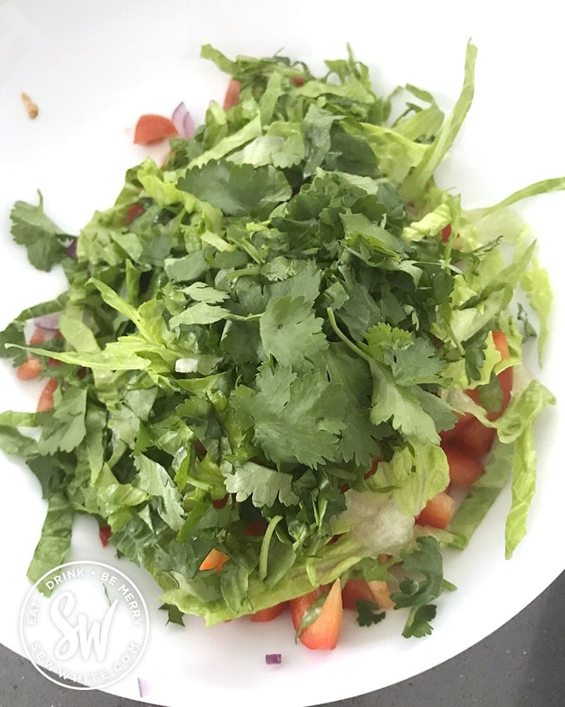 cilantro being added to the fish taco salsa