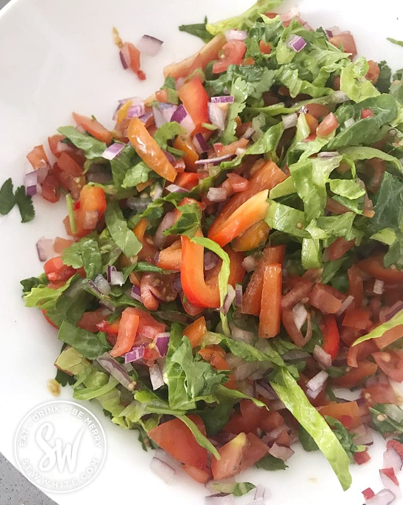 A white bowl with a mix of tomatoes, lettuce, pepper, cilantro, red onion and chilli