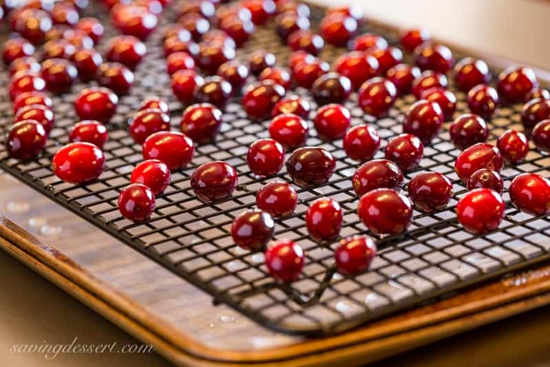 A cooling rack covered with cranberries that have been dipped in a simple syrup