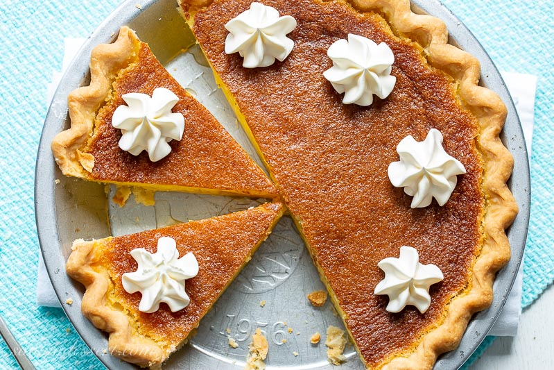 A sliced lemon chess pie topped with swirls of whipped cream