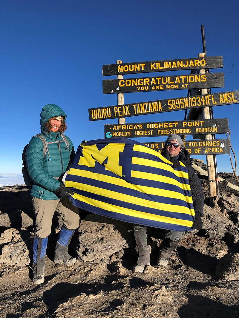 Over the summer, Coleman Harris (left) and his uncle, Jon, '94, flew the Maize and Blue at the top of Mount Kilimanjaro.